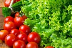 Salada, tomates e cebolinha da alface no fundo de madeira Imagem de Stock