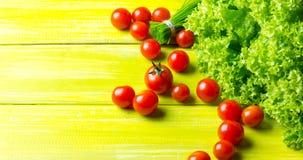 Salada, tomates e cebolinha da alface no fundo verde de madeira Imagem de Stock