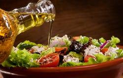 Salada vegetal com o petróleo verde-oliva que derrama de um bott Fotografia de Stock