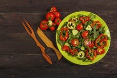 Salada vegetal com os legumes frescos do tamata, dos pepinos, da alface, da cebola e da rúcula em uma tabela de madeira Salada co imagens de stock royalty free