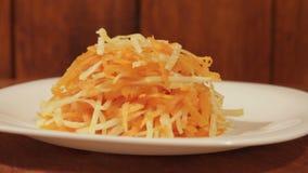 Salada vegetal da cenoura e da couve na placa branca no fim de madeira do fundo acima video estoque
