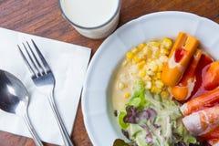 Salada vegetal da manhã com o hotdog no prato e o leite em de madeira Imagem de Stock Royalty Free