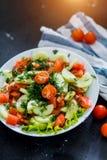 Salada vegetal da mola fresca do tomate e do pepino em um fundo preto, fim acima imagem de stock