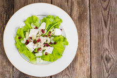 Salada verde com queijo e romã de cabra em um fundo de Imagens de Stock Royalty Free