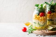 Saladas caseiros saudáveis com bulgur, vegetais e cal em uns frascos de pedreiro no fundo de pedra cinzento Fotos de Stock Royalty Free