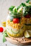 Saladas caseiros saudáveis com bulgur, vegetais e cal em uns frascos de pedreiro no fundo de pedra cinzento Imagens de Stock