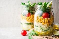 Saladas caseiros saudáveis com bulgur, vegetais e cal em uns frascos de pedreiro no fundo de pedra cinzento Imagens de Stock Royalty Free