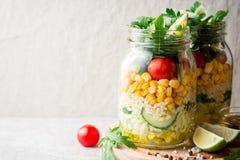 Saladas caseiros saudáveis com bulgur, vegetais e cal em uns frascos de pedreiro no fundo de pedra cinzento Fotografia de Stock