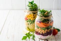 Saladas caseiros saudáveis com grãos-de-bico, bulgur e vegetais em uns frascos de pedreiro no fundo de madeira branco Imagem de Stock Royalty Free