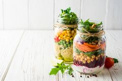 Saladas caseiros saudáveis com grãos-de-bico, bulgur e vegetais em uns frascos de pedreiro no fundo de madeira branco Fotografia de Stock