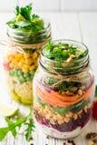 Saladas caseiros saudáveis com grãos-de-bico, bulgur e vegetais em uns frascos de pedreiro no fundo de madeira branco Foto de Stock