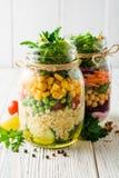 Saladas caseiros saudáveis com grãos-de-bico, bulgur e vegetais em uns frascos de pedreiro no fundo de madeira branco Fotografia de Stock Royalty Free