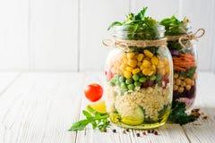 Saladas caseiros saudáveis com grãos-de-bico, bulgur e vegetais em uns frascos de pedreiro no fundo de madeira branco Foto de Stock Royalty Free