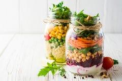 Saladas caseiros saudáveis com grãos-de-bico, bulgur e vegetais em uns frascos de pedreiro no fundo de madeira branco Imagens de Stock Royalty Free