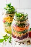 Saladas caseiros saudáveis com grãos-de-bico, bulgur e vegetais em uns frascos de pedreiro no fundo de madeira branco Fotos de Stock