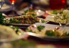 Saladas e placas com aperitivos em uma tabela festiva Fotografia de Stock