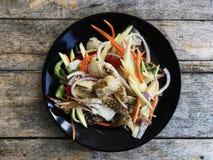 Salade épicée avec le crabe dans le plat noir sur la table de vintage Photos stock