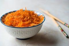 Salade épicée de carotte de style coréen avec des baguettes dans la cuvette photographie stock libre de droits