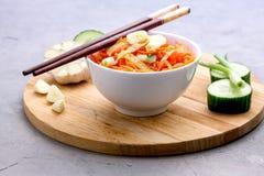 Salade épicée organique de carotte avec le plateau en bois de concept d'aliment biologique de Vegan de concombre et d'ail photographie stock