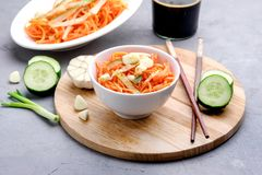 Salade épicée organique de carotte avec le plateau en bois de concept d'aliment biologique de Vegan de concombre et d'ail photos libres de droits