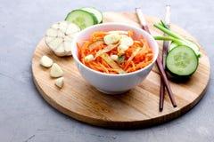 Salade épicée organique de carotte avec le plateau en bois de concept d'aliment biologique de Vegan de concombre et d'ail images stock