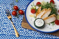 Salade avec de la salade de César de poulet avec des micro-verts, des tomates-cerises et le parmesan sur un fond bleu d'ornement photo stock