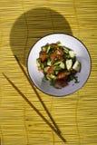 Salade avec des baguettes sur un tapis en bambou jaune sur le fond en bois photo libre de droits