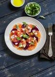 Salade avec des betteraves, des oranges et le fromage à pâte molle d'un plat blanc Photographie stock libre de droits