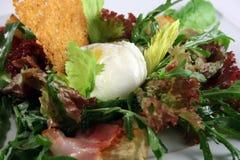 Salade avec des chips d'oeufs pochés et de pain Images stock