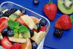 Salade avec des fruits frais et des baies dans une cuvette sur la table en bois bleue photos stock