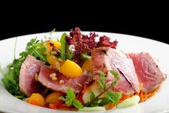 Salade avec des morceaux de thon grillé entre saignant et à point Image stock