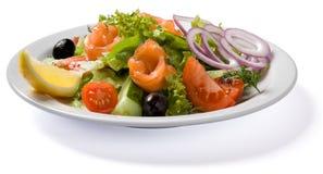 Salade avec des saumons servis de la plaque blanche Image stock