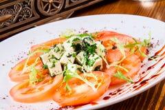 Salade avec des tomates, fromage, herbes Photographie stock libre de droits