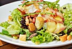 Salade avec du fromage de chèvre, le jambon et les légumes chauds Photographie stock