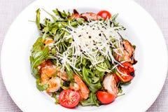 Salade avec l'arugula et les crevettes dans un plat blanc Image libre de droits