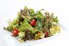 Salade avec l'avocat et les légumes d'un plat blanc images stock