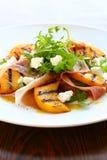 Salade avec la pêche et le jambon grillés Image libre de droits