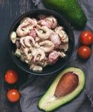 Salade avec la sauce de crevette, d'avocat et tomate dans un plat noir Images stock