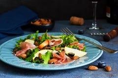 Salade avec le jamon, les poires, les myrtilles et les amandes Photo stock