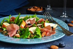 Salade avec le jamon, les poires, les myrtilles et les amandes Photographie stock libre de droits