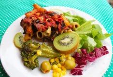 Salade avec le kiwi, la laitue, les olives, le maïs et un morceau de macaronis avec des champignons image libre de droits