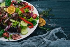 Salade avec le lard et le foie de poulet Sur une surface en bois image libre de droits