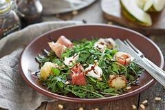 Salade avec le melon et le Prosciutto sur le fond en bois Images libres de droits