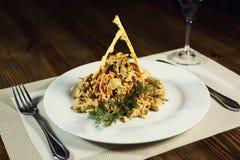 Salade avec le poulet, les champignons et les carottes Plats de portion dans un r Photographie stock