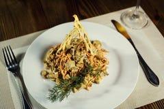 Salade avec le poulet, les champignons et les carottes Plats de portion dans un r Photos stock