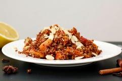 Salade avec le quinoa, la pomme et la carotte rouges avec l'amande du plat blanc sur le fond noir images stock