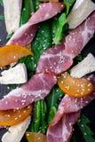 Salade avec le serrano de jamon de jambon, camembert, melon, arugula de plat en pierre noir d'ardoise sur le fond noir Vue supéri Photographie stock libre de droits