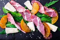 Salade avec le serrano de jamon de jambon, camembert, melon, arugula de plat en pierre noir d'ardoise sur le fond noir Vue supéri Photos stock