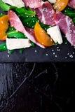 Salade avec le serrano de jamon de jambon, camembert, melon, arugula de plat en pierre noir d'ardoise sur le fond noir Vue supéri Photo libre de droits