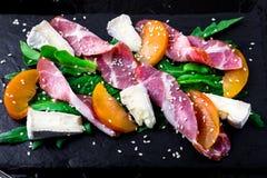Salade avec le serrano de jamon de jambon, camembert, melon, arugula de plat en pierre noir d'ardoise sur le fond noir Vue supéri Images stock